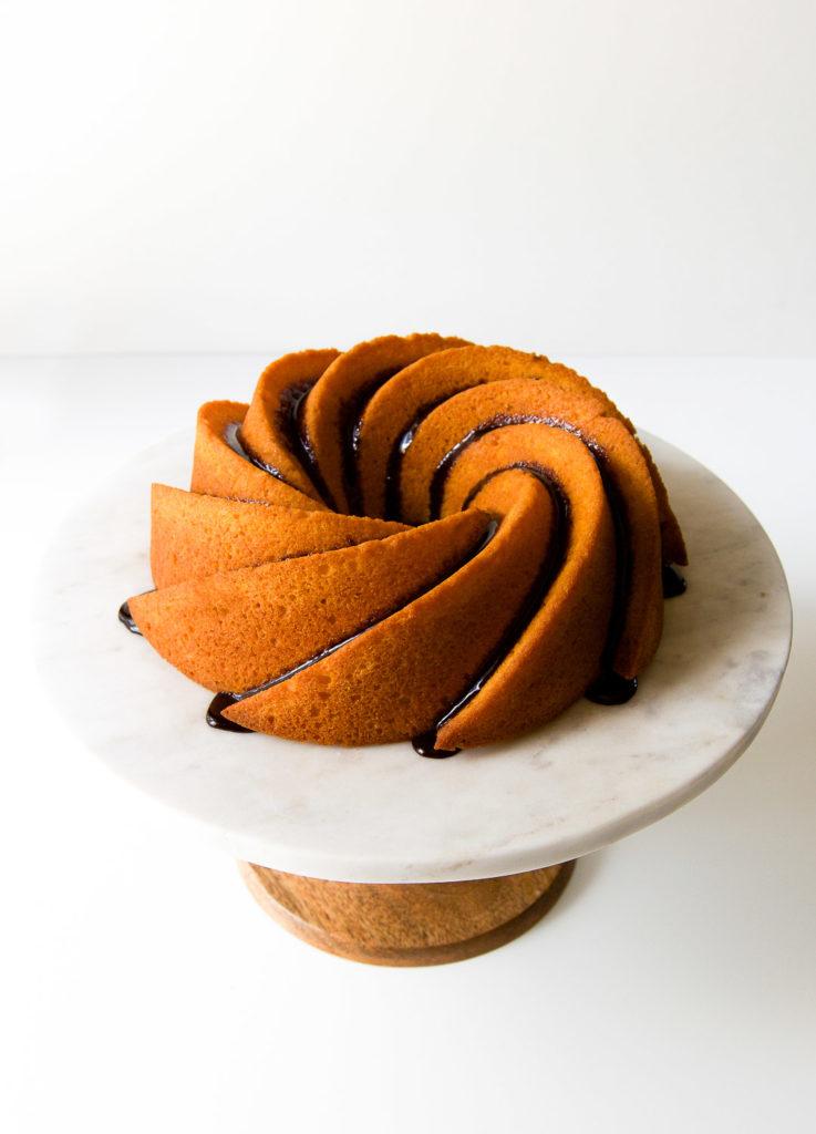 A chocolate-glazed Brazilian bolo de cenoura sits on a cake stand