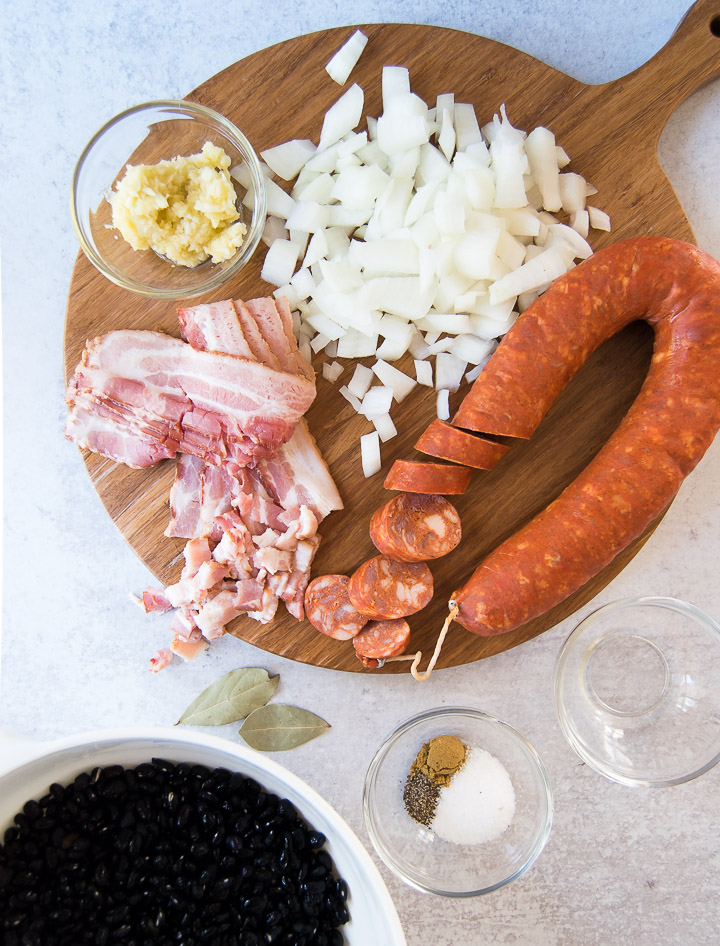 A wooden cutting board holds a sausage, bacon, sofrito and onion next to a bowl of black beans