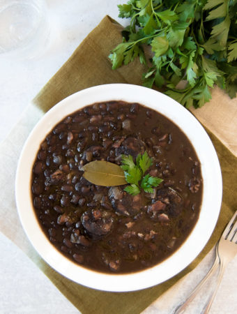 A white bowl holds Brazilian Black Beans, garnished with parsley and a bay leaf