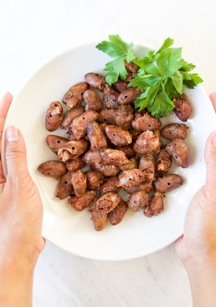 A bowl with grilled chicken hearts and parsley.
