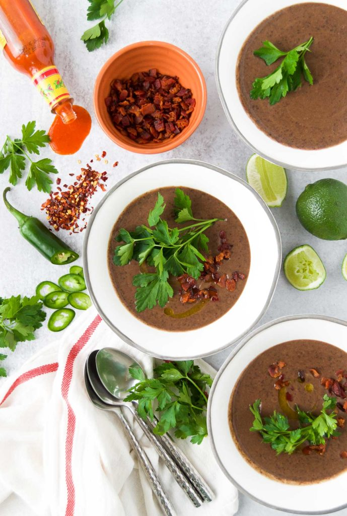 Creamy Black Bean Soup with different toppings.