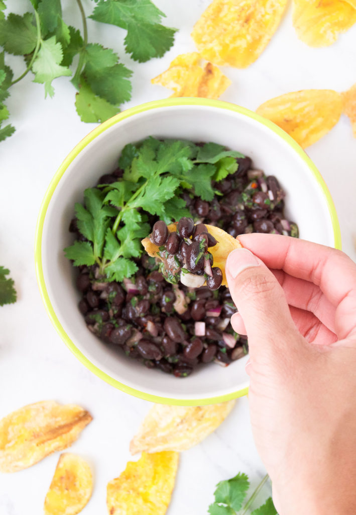 Black Bean Salsa in a bowl with cilantro and plantain chips.