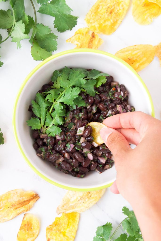 Scooping Black Bean Salsa from a bowl with cilantro with plantain chips.