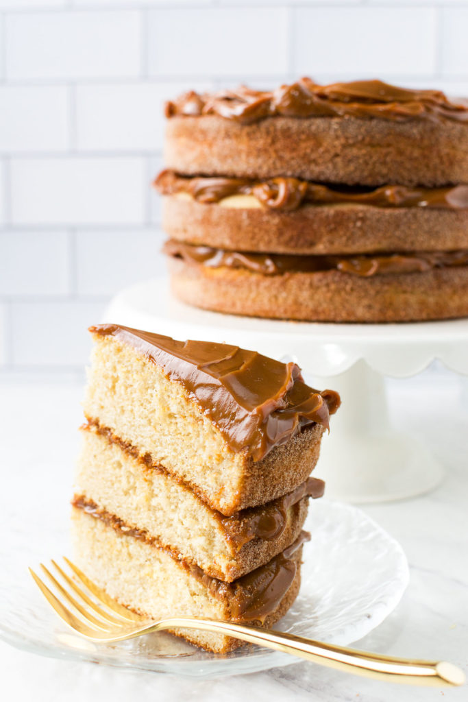 A slice of Brazilian Churro Cake filled and topped with dulce de leche
