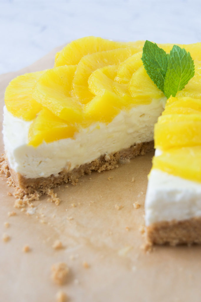 A no bake pineapple cheesecake missing a slice.