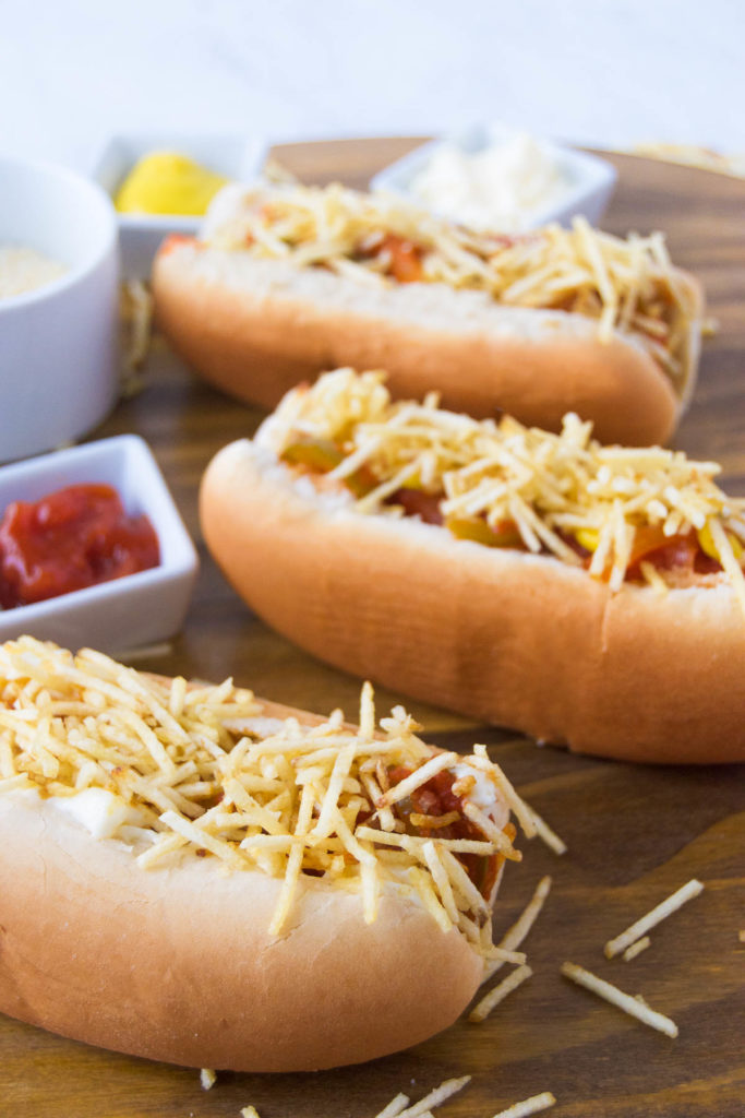 Brazilian Hot Dogs spread with sauce and toppings