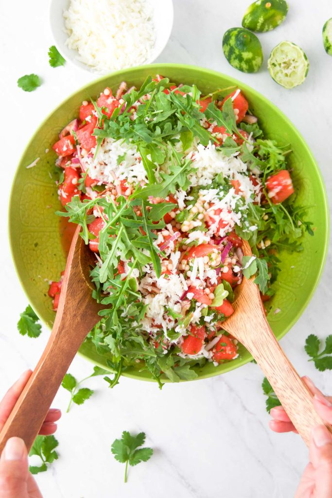 Watermelon Salad Recipe being tossed with Cilantro Honey Lime Dressing