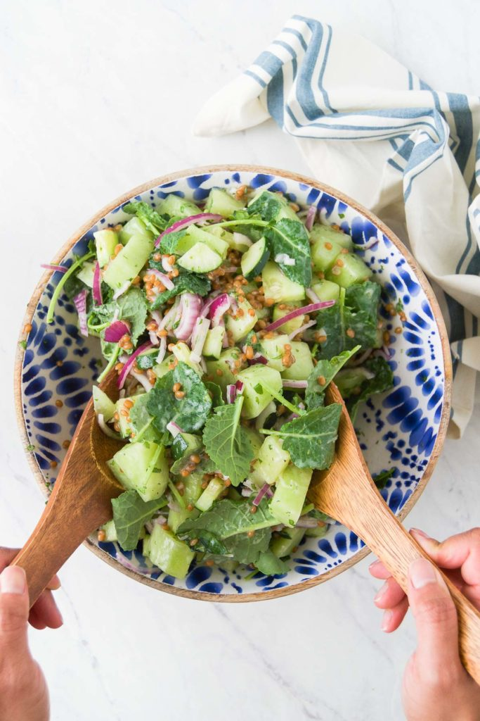 Hands toss Melon Salad with Honey Yogurt Dressing with wooden utensils in a blue bowl