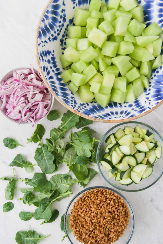 Ingredients for a melon salad on a tabletop in bowls