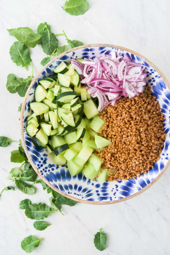 Honeydew melon, cucumber, red onion and wheat berries in a blue patterned bowl with kale on the countertop next to it