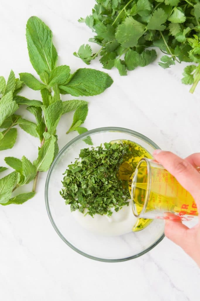 Olive oil is poured over chopped fresh herbs in a bowl