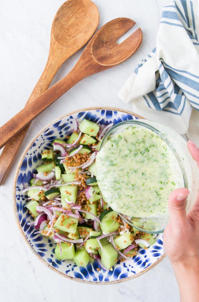 A hand pours Honey Yogurt Dressing over a melon salad