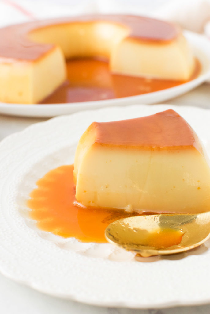 A slice of flan on a white plate with a spoon and the whole flan behind it
