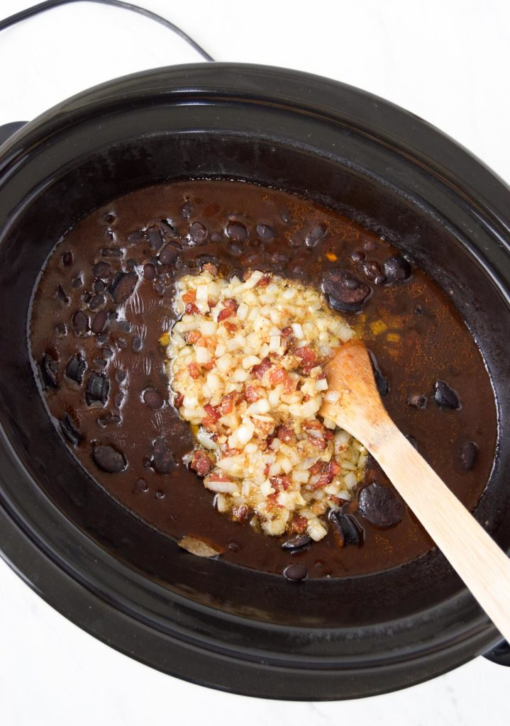 A wooden spoon stirs refogado into the crockpot black beans
