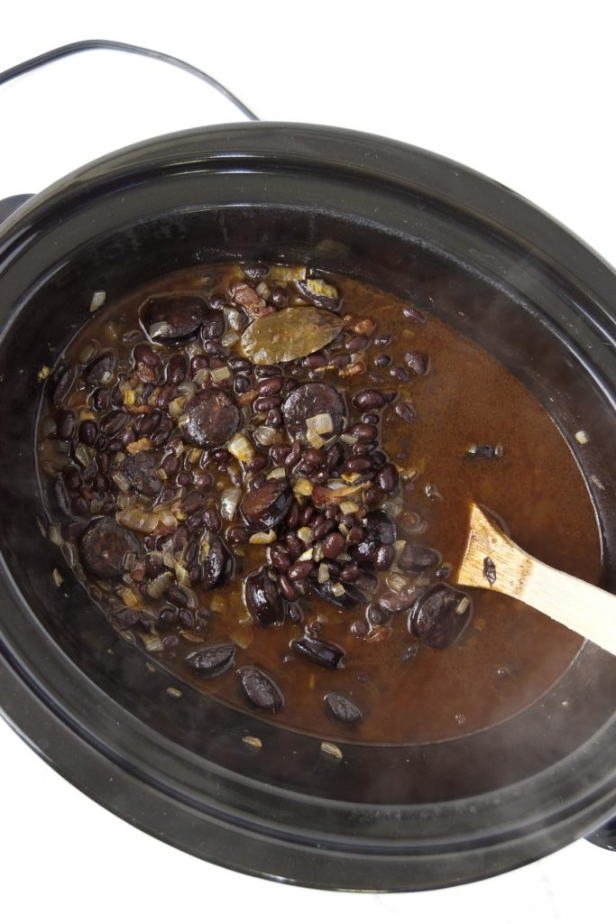 The final slow cooker black beans in a slow cooker being stirred with a wooden spoon