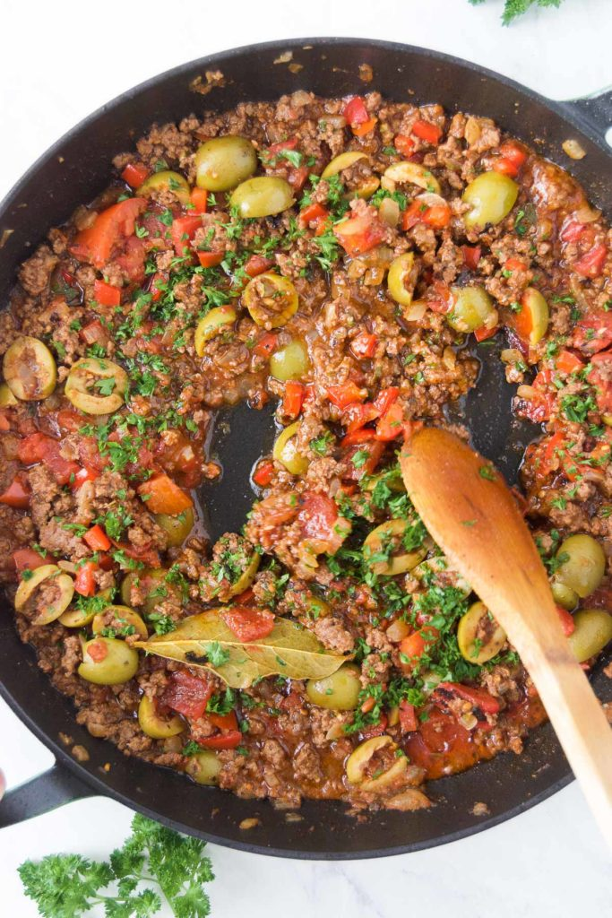 A wooden spoon stirs fresh parsley into a picadillo in a black skillet
