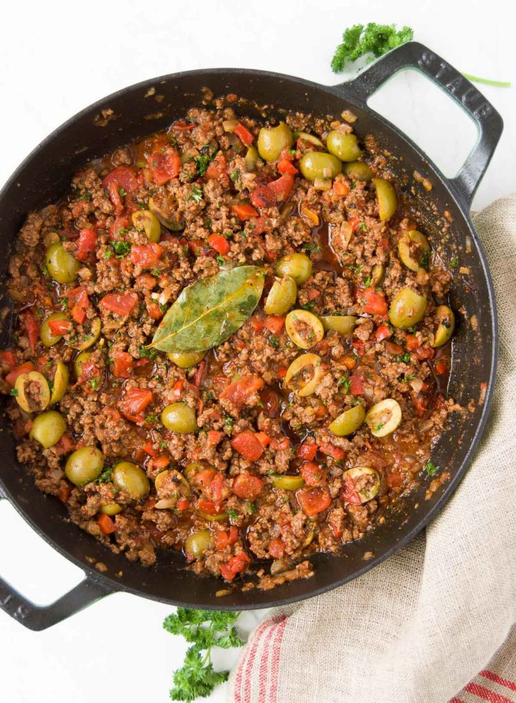 Brazilian Picadillo in a black braising pan sits on top of a red and beige striped towel