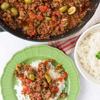 Picadillo is served over rice in a bright green bowl next to a pan holding more picadillo and a bowl holding extra rice