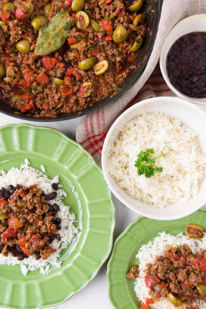 Green bowls hold servings of Brazilian picadillo over rice with beans and sit next to a skillet holding more picadillo and bowls holding rice and beans