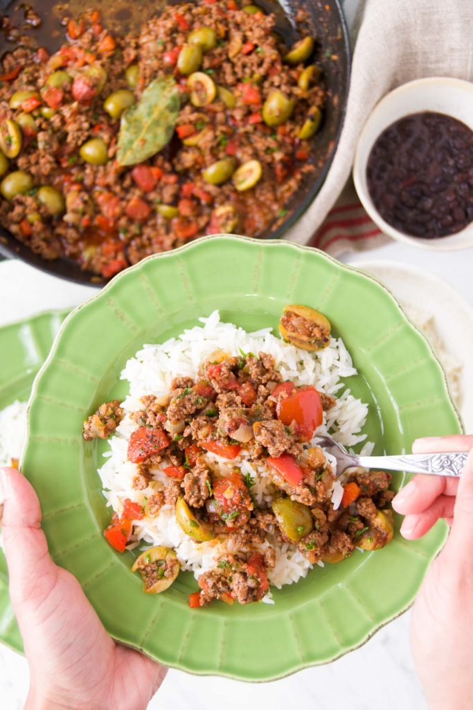 A person holds a utensil in picadillo over rice inside a green bowl