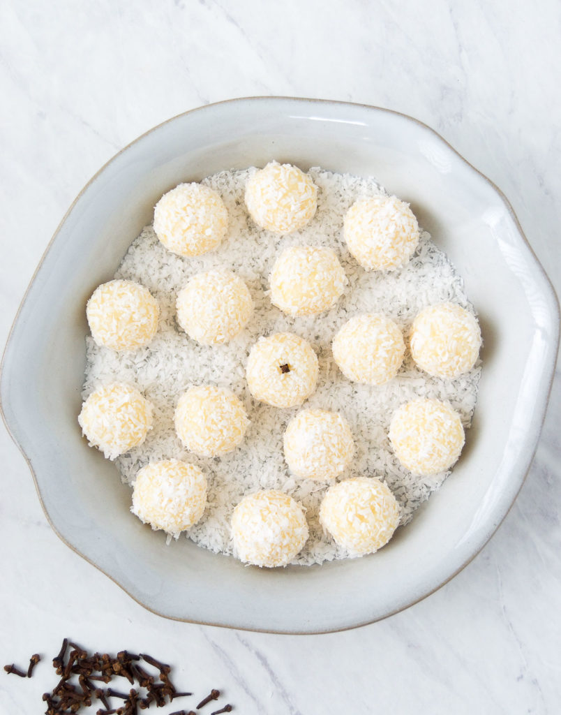 Overhead image of coconut fudge balls in a scalloped light gray dish garnished with coconut on marble