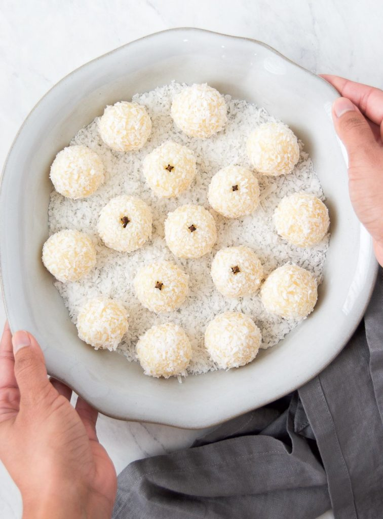 A person holds a scalloped gray dish holding shredded coconut fudge balls with whole cloves