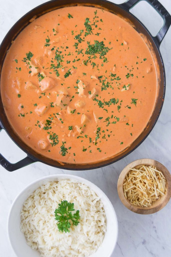 A large pan holding the final Chicken Stroganoff next to a bowl of white rice and potato sticks