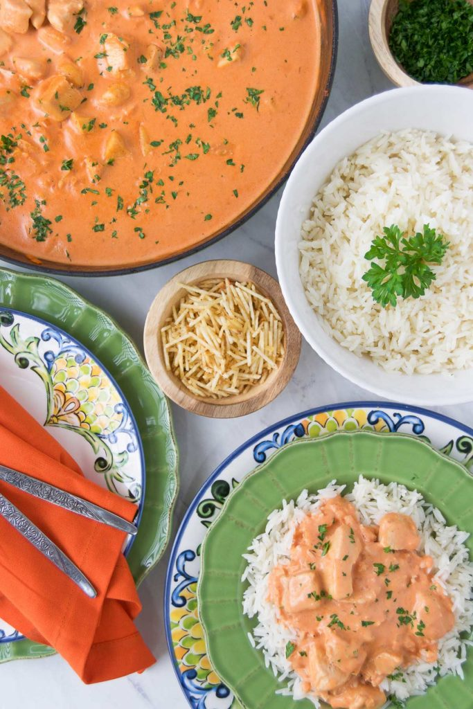 Chicken stroganoff in a green bowl over rice with the stroganoff, a bowl of rice and potato sticks surrounding it in colorful bowls