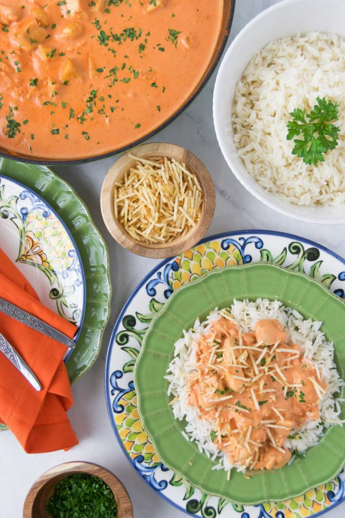 Brazilian Chicken Stroganoff over rice with potato sticks on a green bowl next to the ingredients in separate bowls