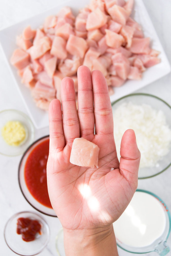 A hand holds a cube of chicken above the ingredients for chicken stroganoff