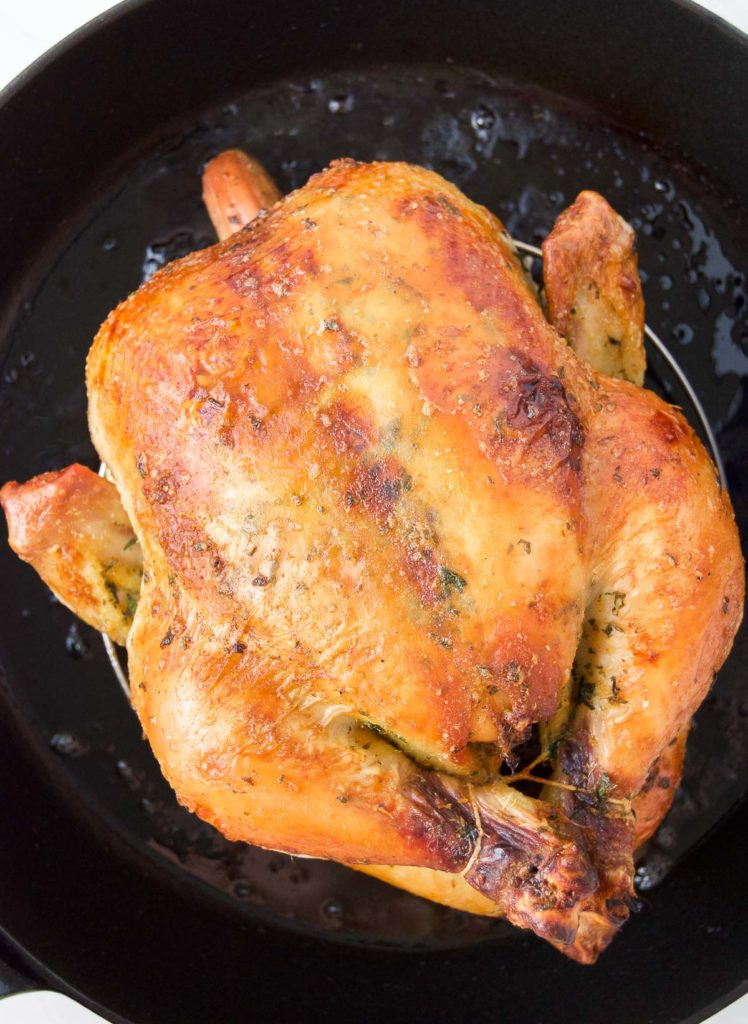 Close up of a trussed Rotisserie-Style Brazilian Chicken after baking in a cast iron roasting pan
