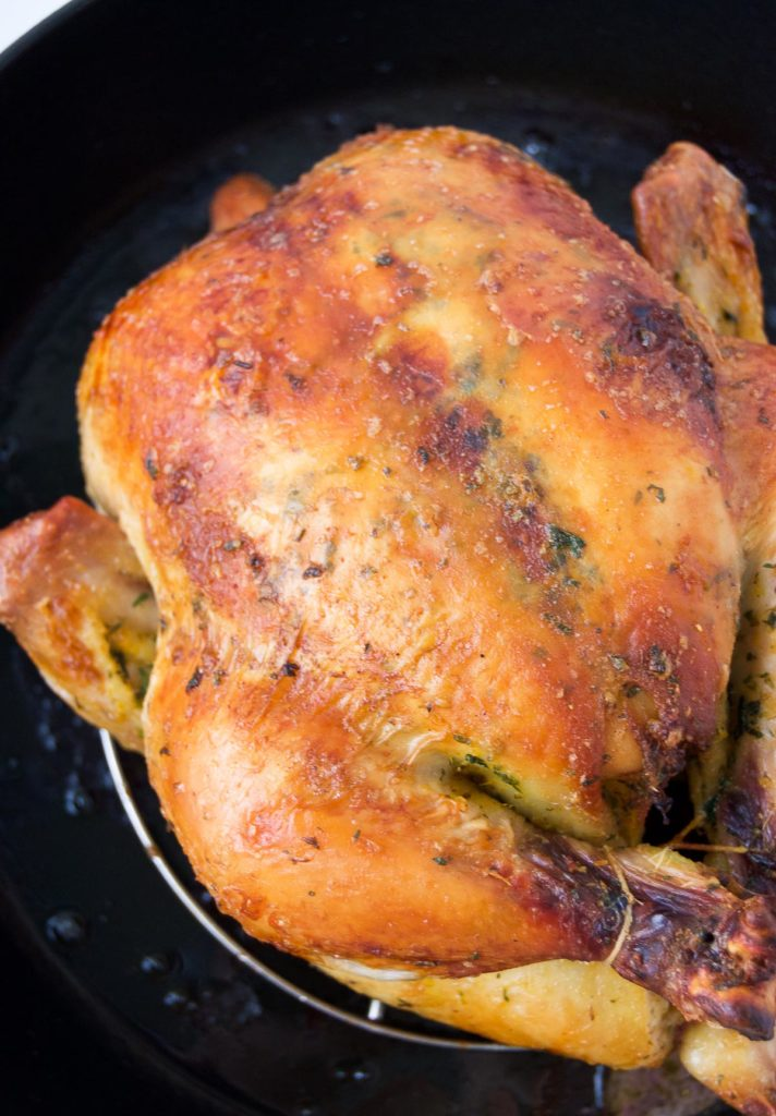 Close up of a Rotisserie-Style Brazilian Chicken in a cast iron roasting pan