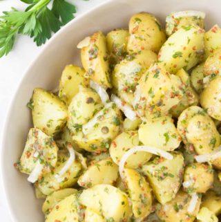 Vegan potato salad in a bowl next to fresh parsley