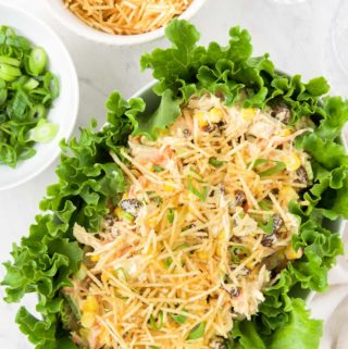 Brazilian chicken salad in a serving dish, surrounded by salad greens