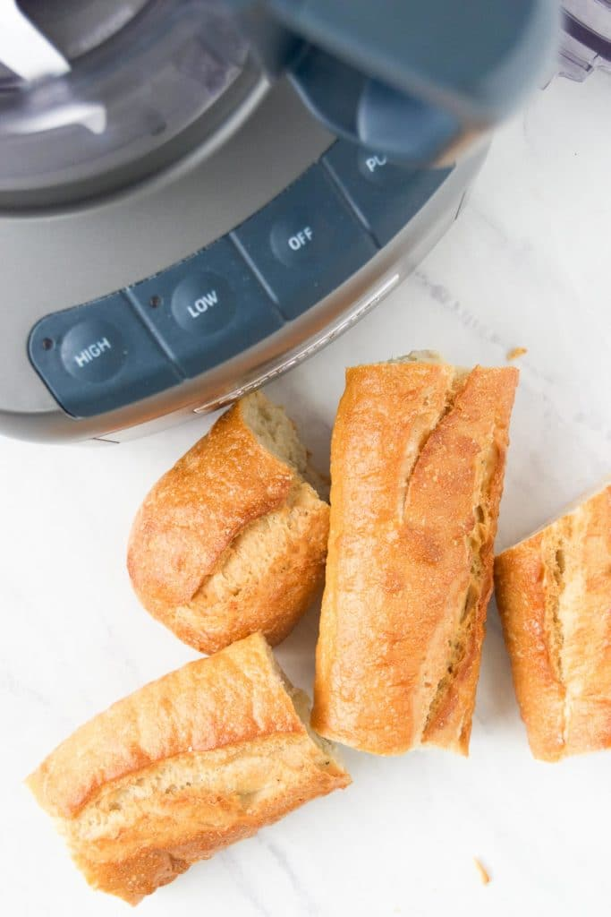 A loaf of bread sits next to a food processor