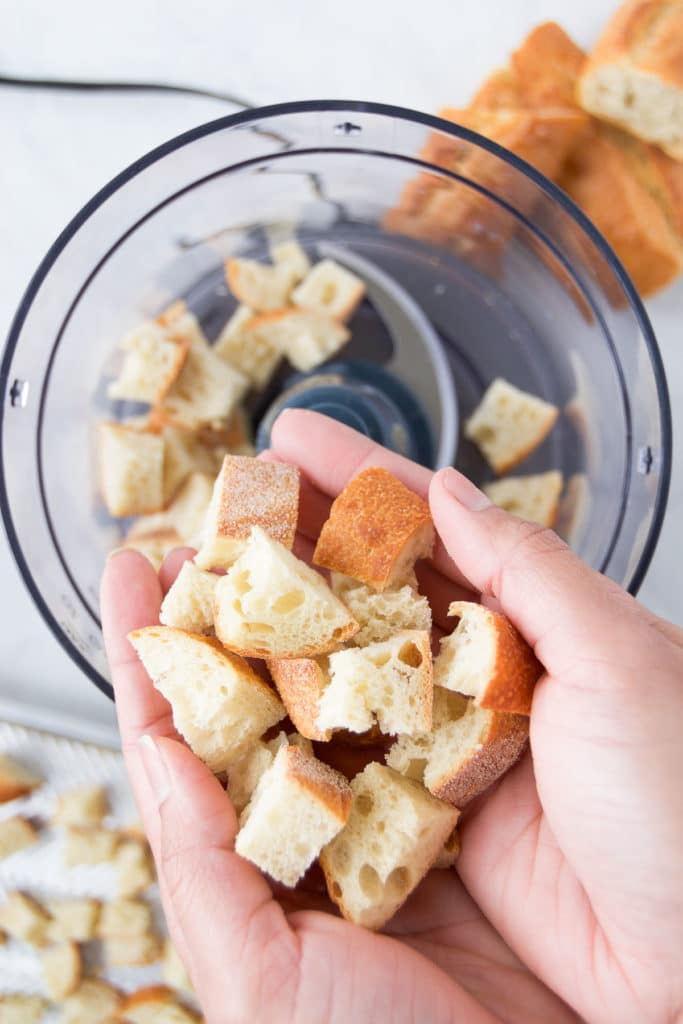 A hand drops baked bread chunks into a food processor