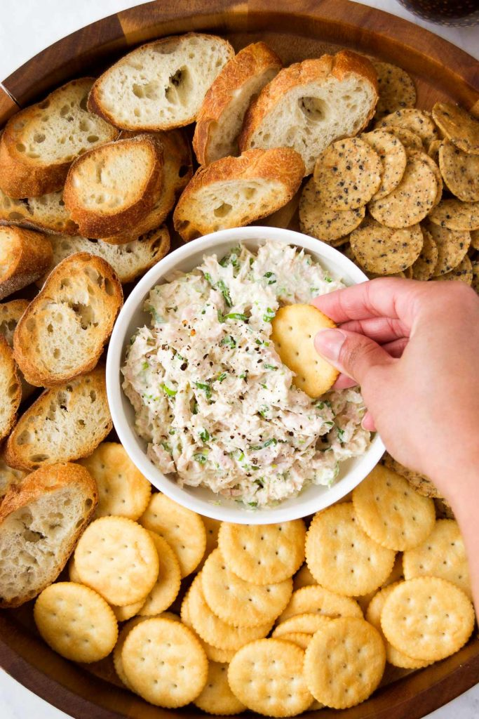 A hand dips a cracker into Pastinha de Atum