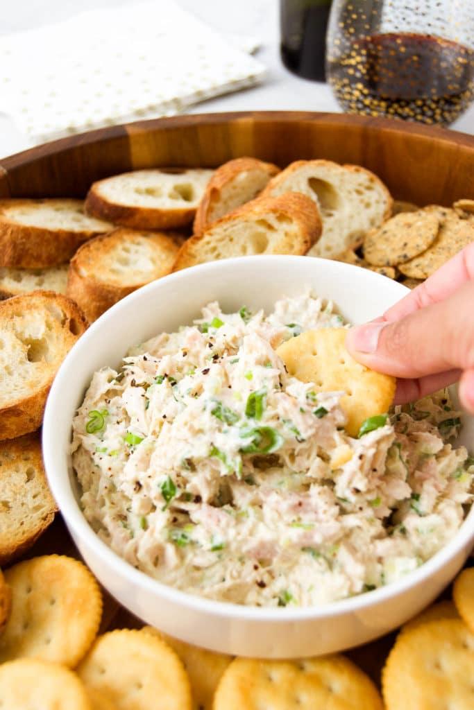 A hand dips a cracker into a bowl of Pastinha de Atum