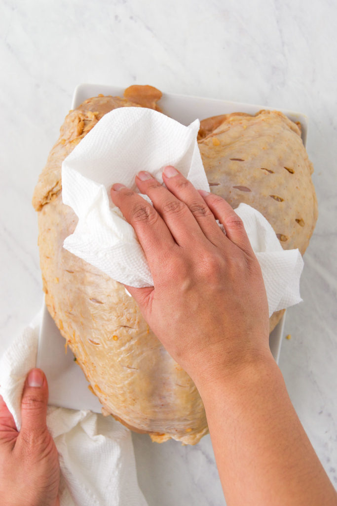 A hand pats a turkey breast dry with a paper towel