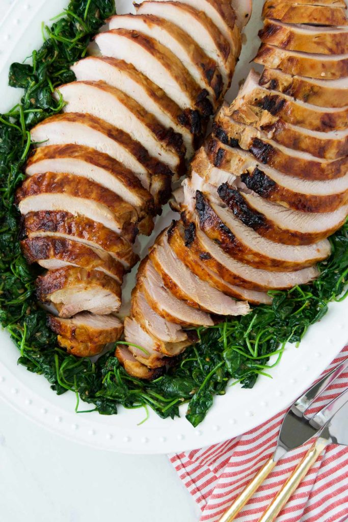 Sliced grilled turkey breast on a plate with greens