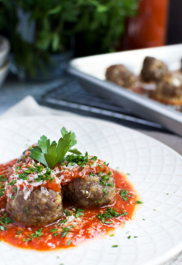 Ground beef and sausage meatballs in tomato sauce with fresh basil