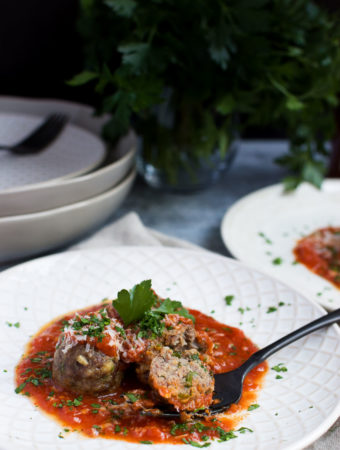 A fork holds a sliced meatball in tomato sauce on a plate